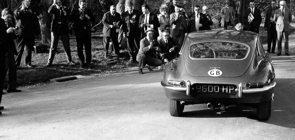 The press gathers around the Jaguar E-Type at its 1961 unveiling by Lake Geneva